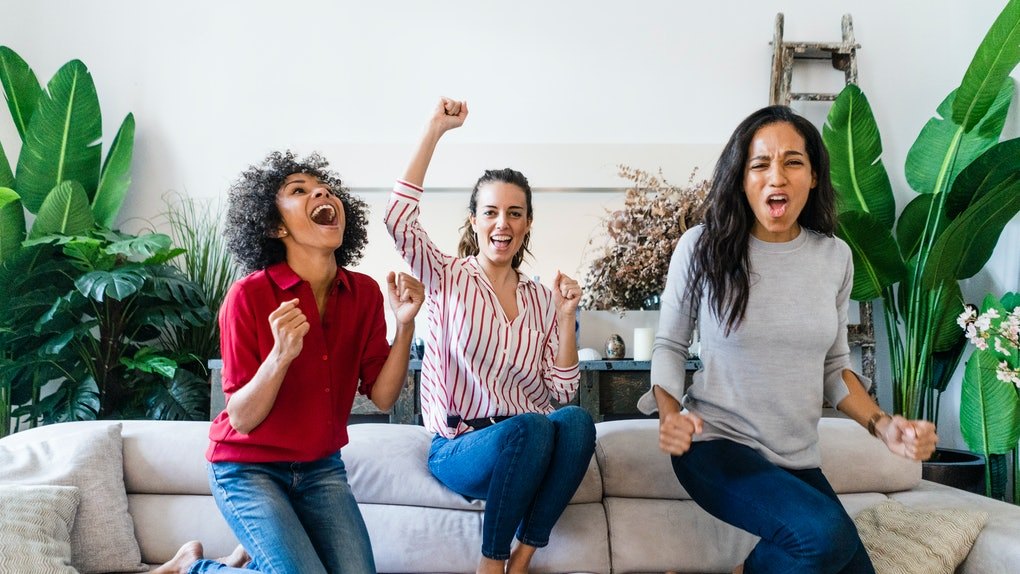 Three friends sit on a couch and cheer for their favorite team during the 2020 Super Bowl.