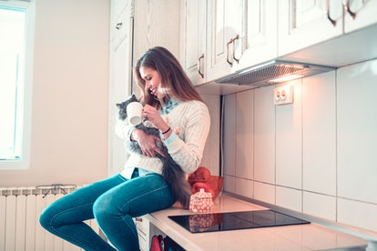 A brunette woman in jeans and a white sweater sits on a counter top with her cat.