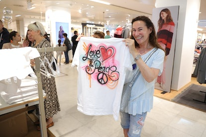 A woman holds an airbrushed T-shirt, another big 2000s fashion trend.