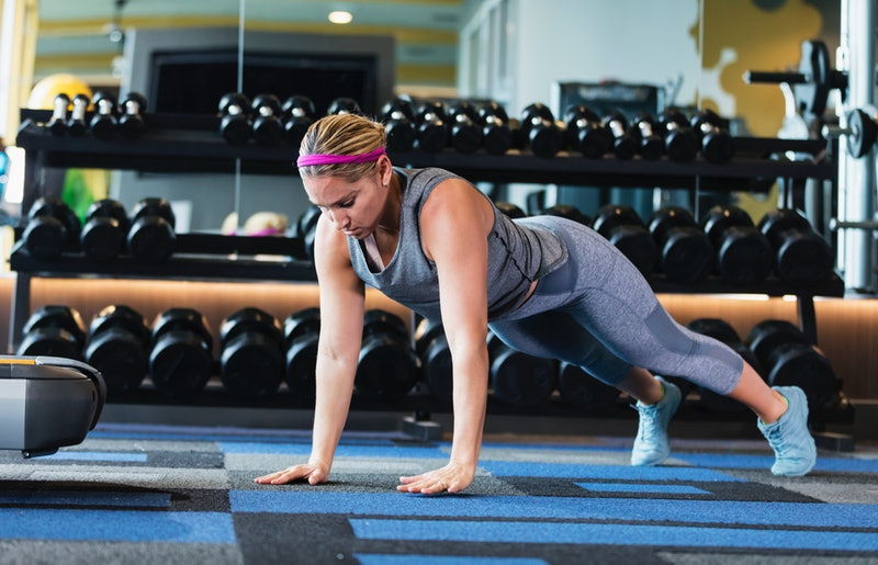 A woman does a pushup, a component of many body positive HIIT workout videos.