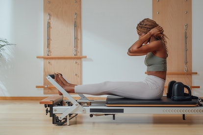 A person prepares to practice Pilates on a reformer. Pilates doesn't require equipment, but reformer...