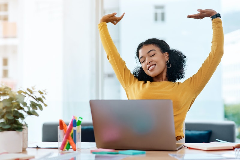 A person in a yellow sweater with a laptop and highlighters on her desk stretches her arms overhead. Stretching at your desk is a great way to boost your productivity and flexibility during your work day.
