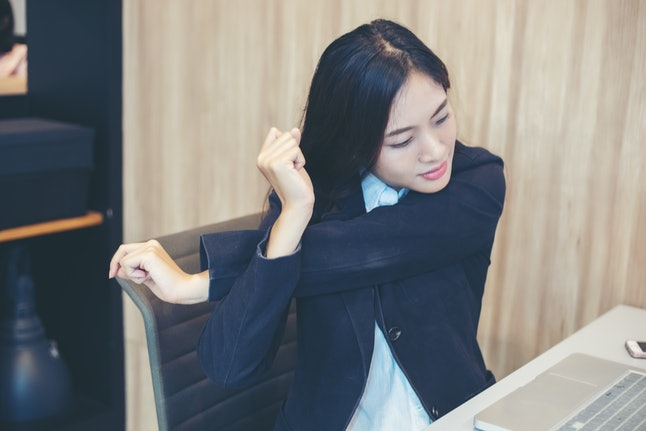 A person stretches her shoulders while sitting at her desk. There are a lot of stretches you can do during work while sitting in your desk chair.