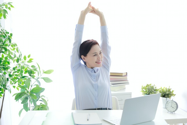 A person sits at a white desk with indoor plants and stretches her arms above her head. Reaching your arms overhead can do a lot to recharge your blood flow and energy levels.