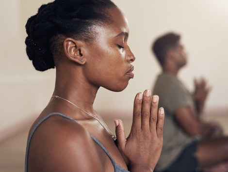 A person folds her hands in front of her chest with her eyes closed during yoga class. Yoga and Pilates both offer excellent fitness benefits, but which one is best for you?