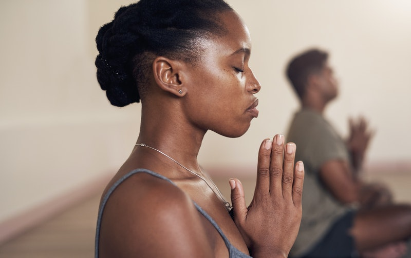 A person folds her hands in front of her chest with her eyes closed during yoga class. Yoga and Pila...