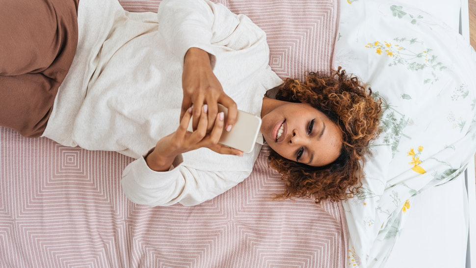 A woman uses her phone in bed first thing in the morning. Blue light's effects on sleep are variable, new research is showing.