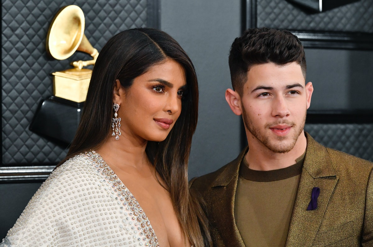 Priyanka Chopra wears a white embellished gown and stands next to husband Nick Jonas on the 2020 Grammys red carpet.