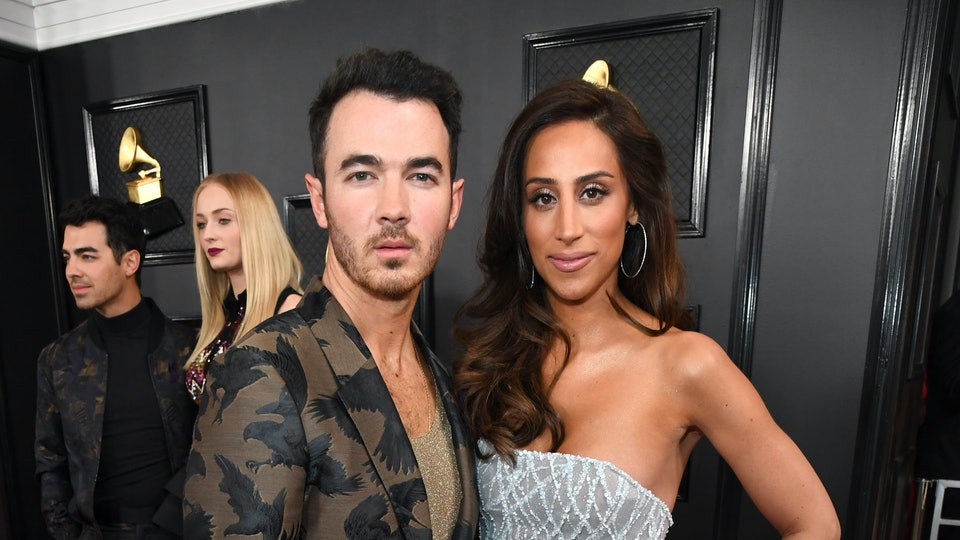 Kevin Jonas and wife Danielle standing on Grammys red carpet