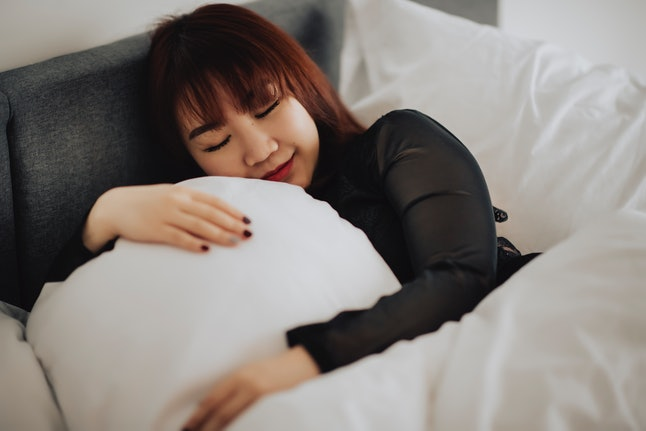 A woman sleeps in a bed. Sleep paralysis is more common in people with a particular genetic variation, but environmental factors can help cause it too.