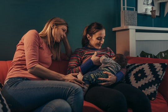 two women sitting on a couch, one breastfeeding