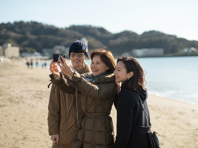 husband, wife, and mother-in-law on a beach taking a selfie