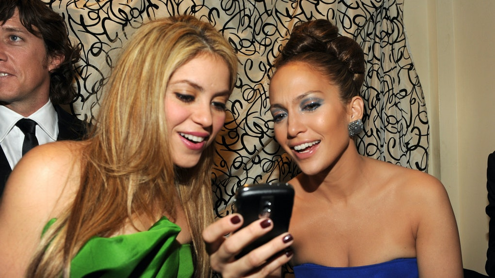 The 2020 Super Bowl halftime show performers, Shakira and Jennifer Lopez, are looking at J.Lo's phone together and smiling.