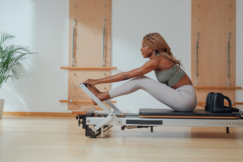 A person prepares to do Pilates exercises on a reformer. Pilates has a lot of potential mental health benefits, according to studies.