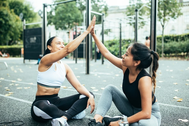 A woman high fives her personal trainer. Personal training has some similarities to finding a therapist.
