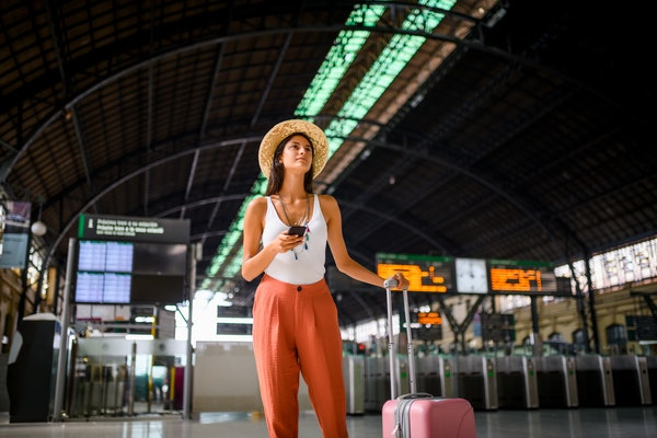 A young woman in a summery outfit stands in an airport with her pink carry-on bag and phone.