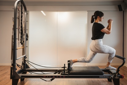 A person exercises on a Pilates reformer. Pilates can help reduce symptoms of depression and anxiety.