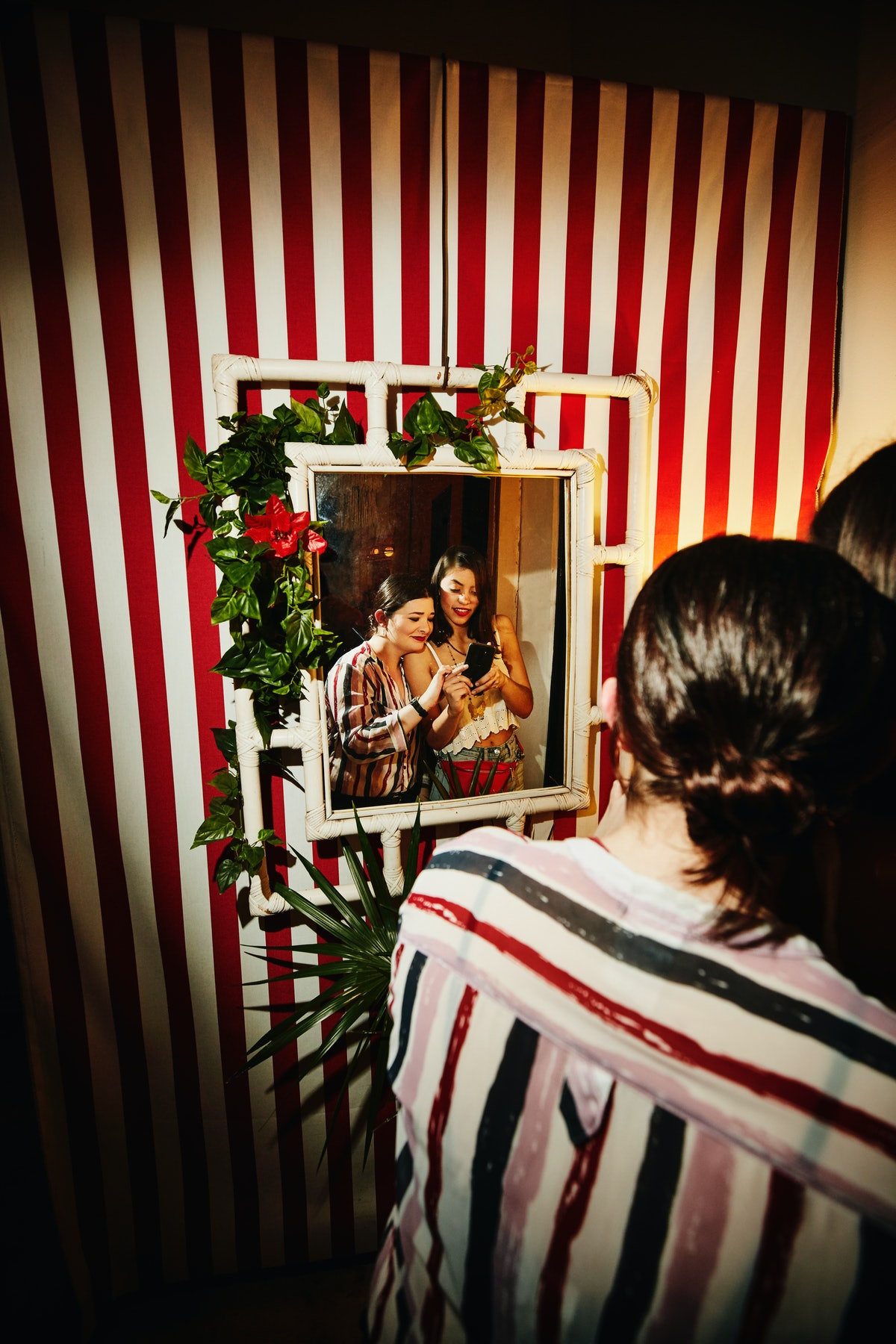 Two women smile and pose in front of a cool mirror on a striped wall for a selfie.