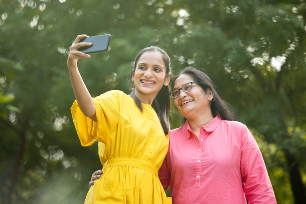A woman in a yellow sundress poses with her mom for a selfie in a park.