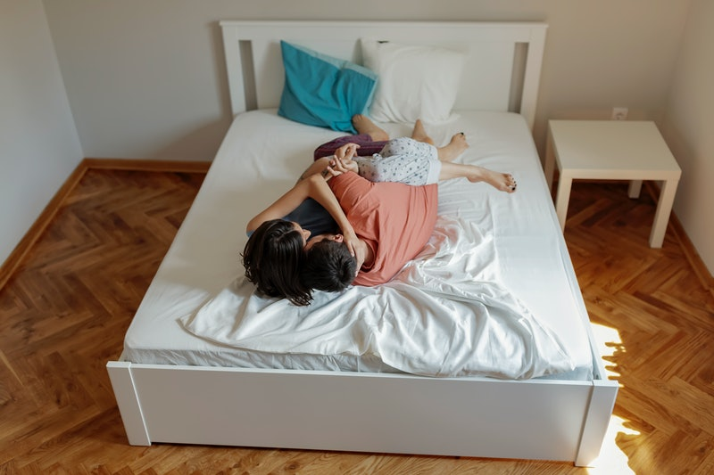 A couple lies in bed together. Ways to help a guy last longer in bed depend on your relationship.