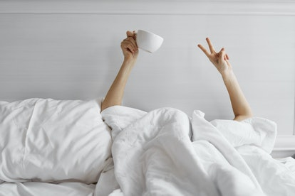 A woman in bed with tea. Alcohol disrupts sleep, so sobriety can improve sleep quality - and that can also help anxiety symptoms.