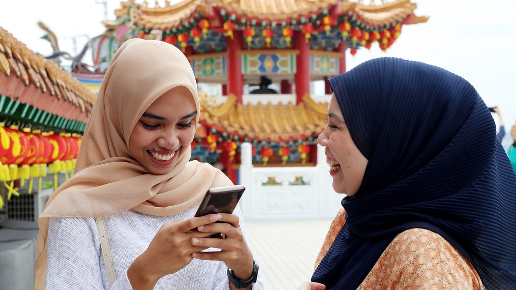 Two friends laugh and play on a phone while at a colorful temple on the Lunar New Year.