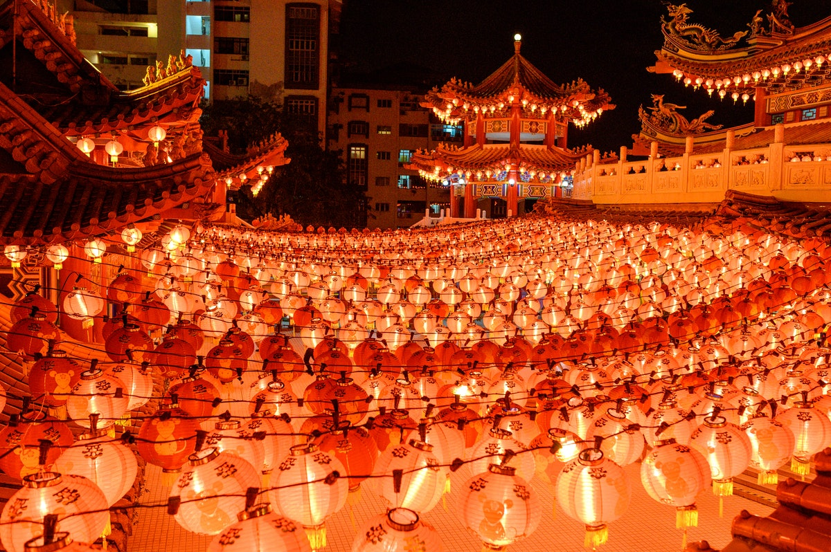 A colorful temple is surrounded by bright, red lanterns for the Lunar New Year.