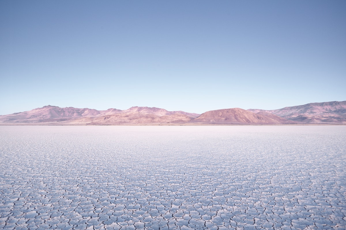 The Alvord Desert in Oregon features a cracked ground and faded mountains, and is perfect for an engagement photo shoot.