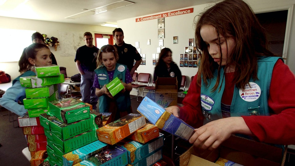 girl scouts sorting boxes of cookies