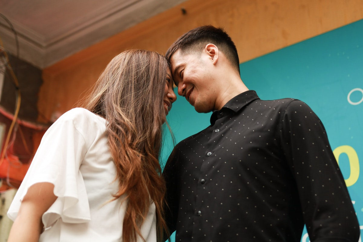 A young couple share a romantic moment in front of a colorful wall during an engagement photo shoot.