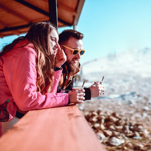 A couple enjoys cups of hot chocolate while on a romantic ski trip.