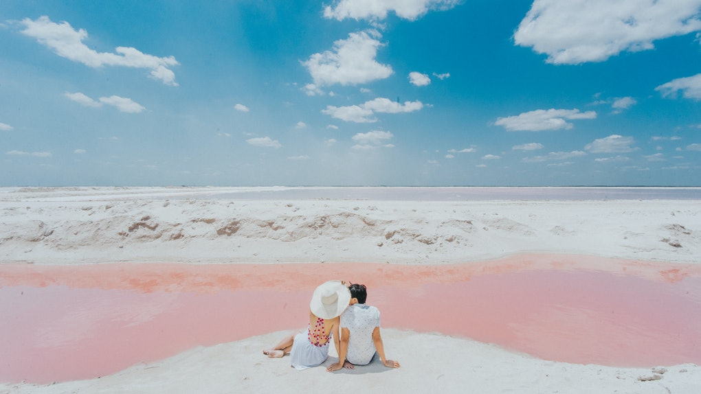 A couple shares a romantic moment on a pink beach while on a 25th birthday trip.