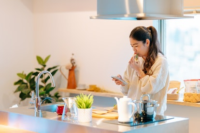 A woman eats vegetables while looking at her phone, where she's gotten an alarm reminder. Setting an alarm is one of the best hacks to stop forgetting things for good.