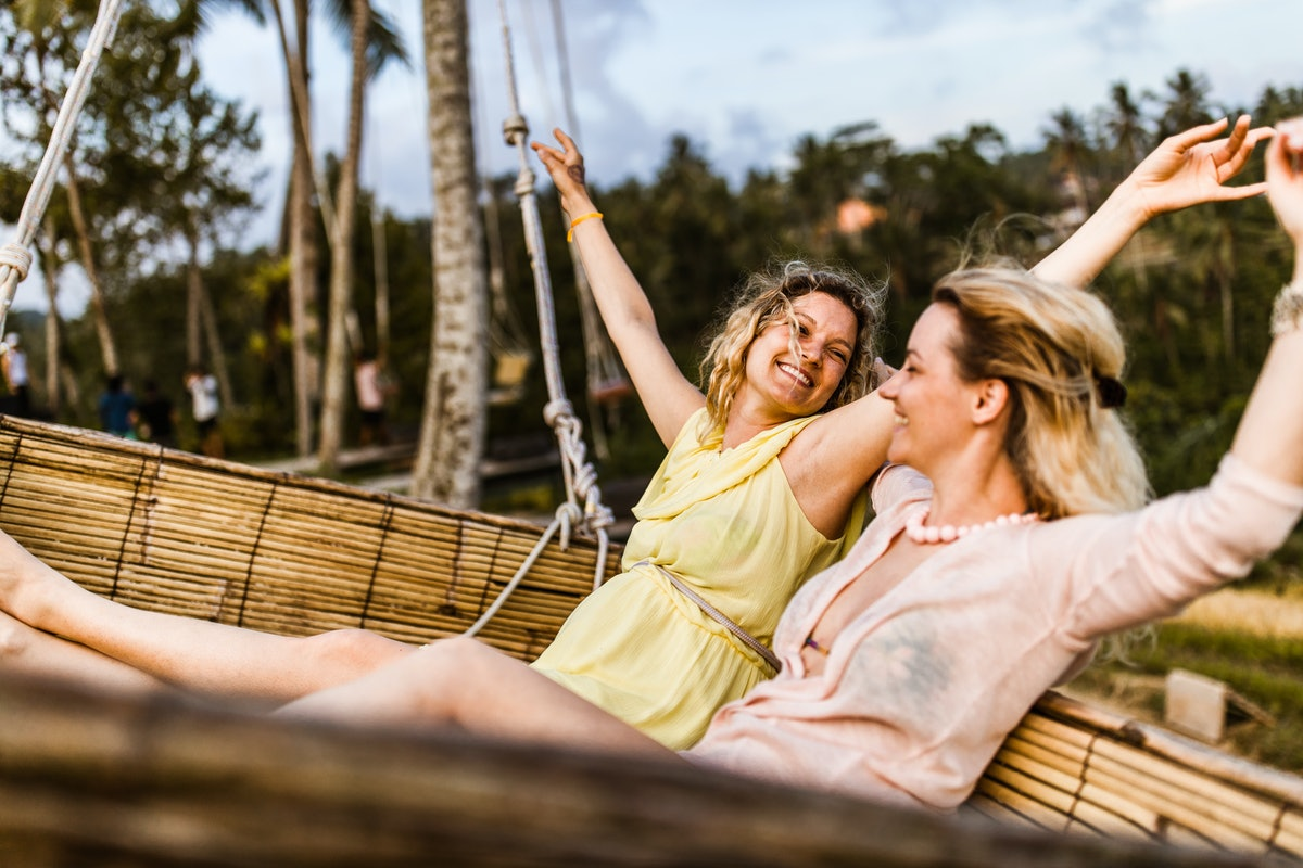 Two friends swing amongst palm trees while on a vacation in Ubud, Bali.