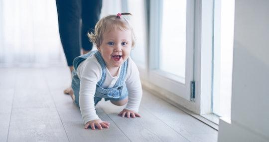 a baby girl crawling down a hallway