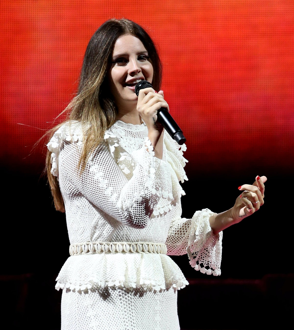 Lana Del Rey hits the stage in a ruffled white dress.