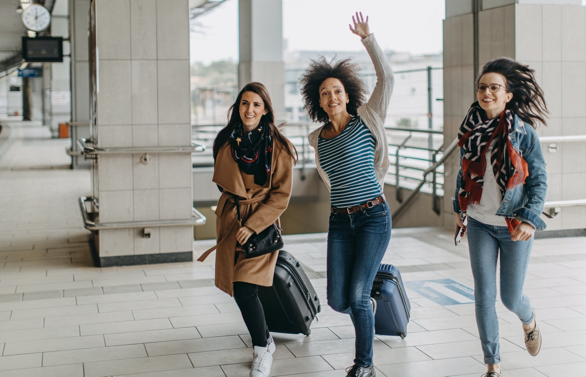 Three friends run through an airport with their suitcases because they're running late.
