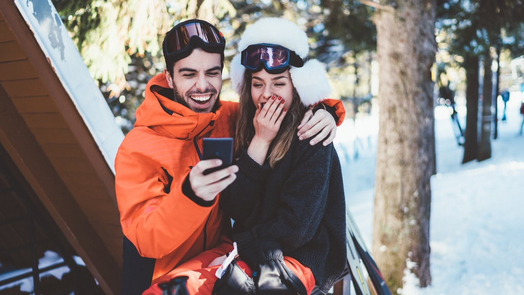 A couple laughs while taking a selfie on their phone during a ski trip.