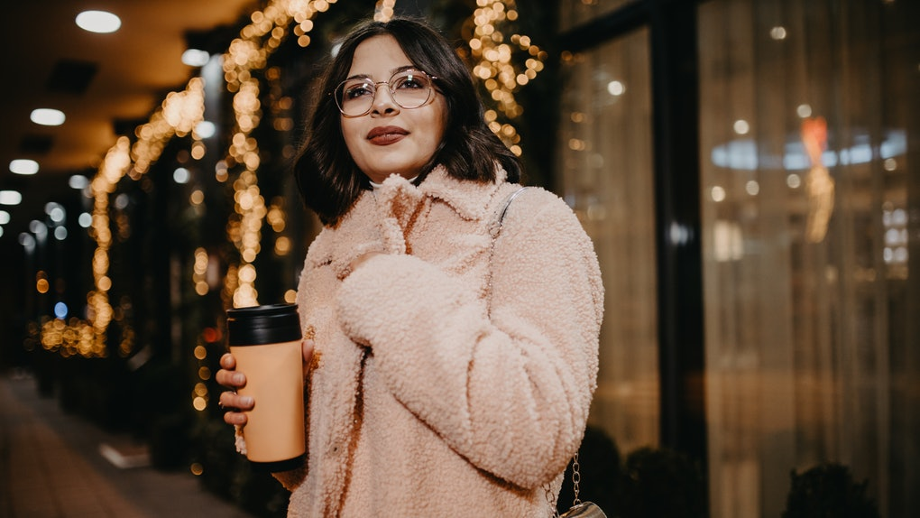 A brunette woman wearing glasses and a light pink coat stands on a sidewalk at night in the city.