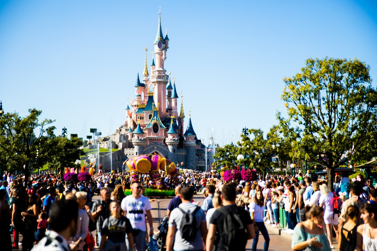 Crowds of people gather around Cinderella's castle in Disneyland Paris on a sunny day.