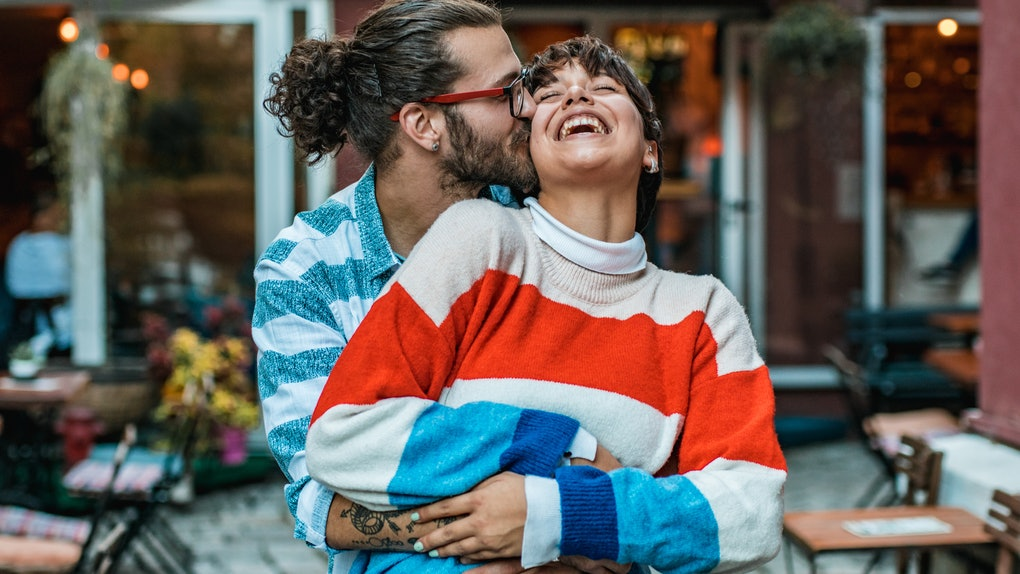A hipster-looking couple hugs and laughs at an outdoor café.