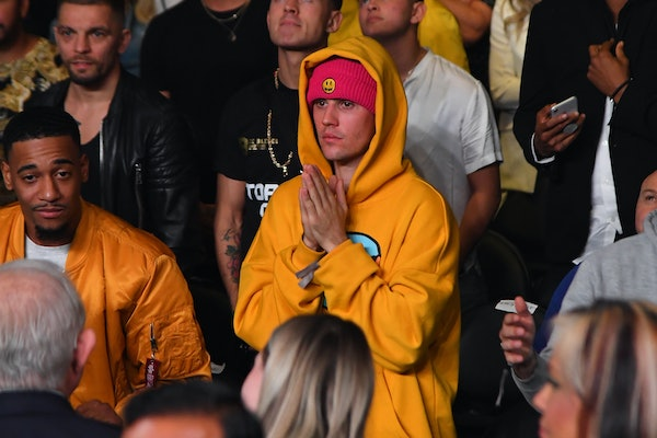 Justin Bieber is spotted in the crowd rocking a yellow hooded sweatshirt.
