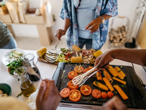 """A family cooks a meal of grilled vegetables. The term """"clean eating"""" is often too vague to be meaningful, but any kind of restrictive diet like clean eating can have negative effects on your body."""