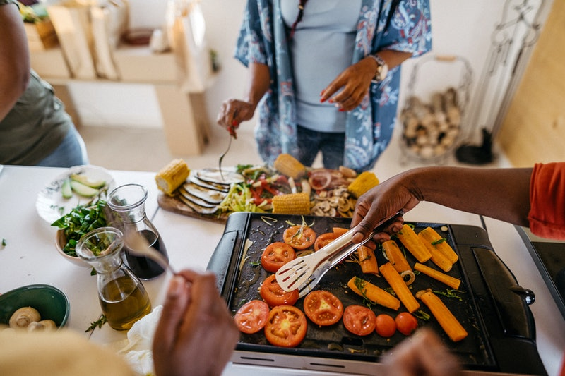 "A family cooks a meal of grilled vegetables. The term ""clean eating"" is often too vague to be meaningful, but any kind of restrictive diet like clean eating can have negative effects on your body."