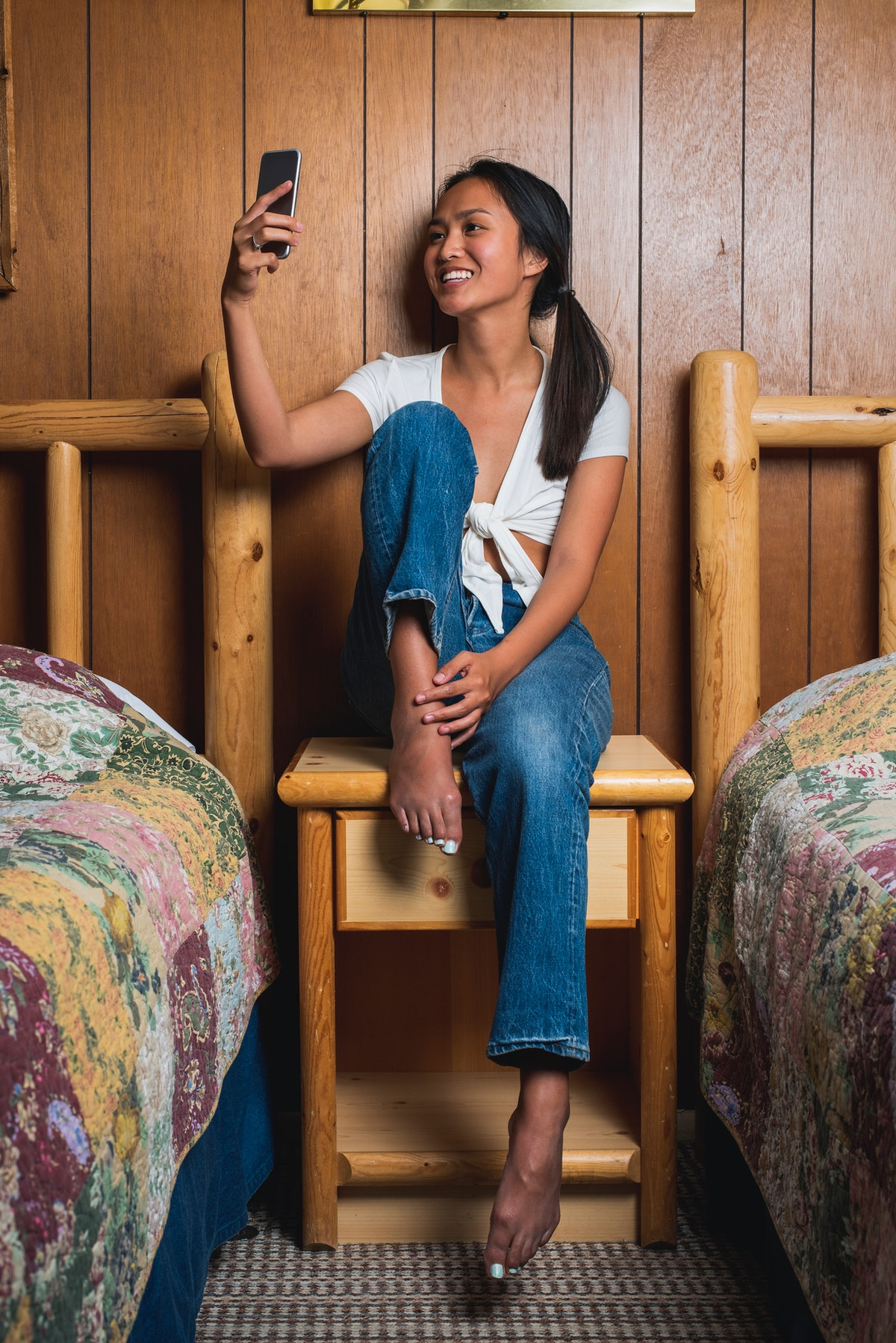 A young Asian woman takes a selfie on her phone while sitting on a wooden nightstand in between two beds during a fall staycation.