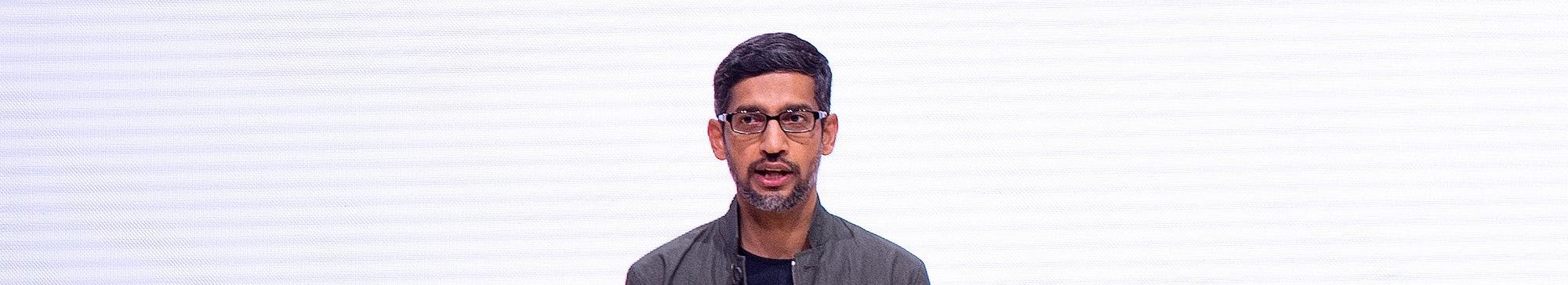 "Google CEO Sundar Pichai in front of the Google ""G"" letter."