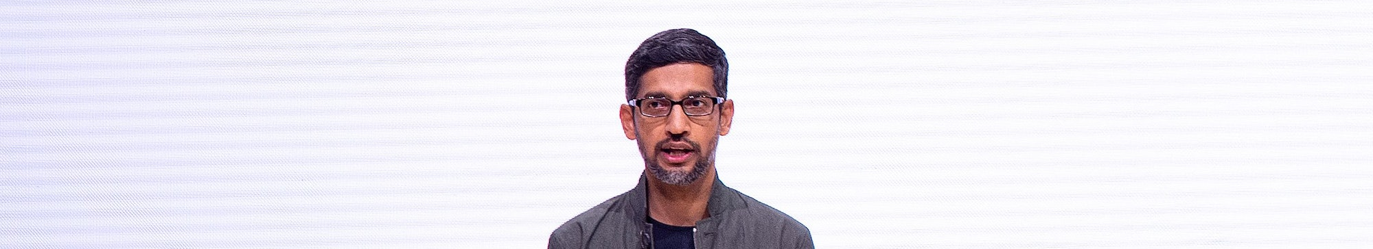 "Google CEO Sundar Pichai in front of the Google ""G"" letter."