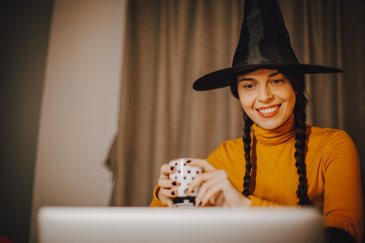 A woman with a witch's hat, orange turtleneck, and braids smiles while holding a Halloween mug.