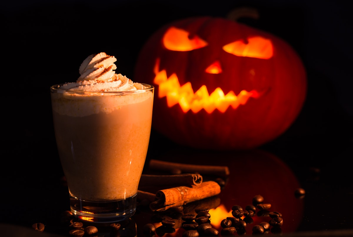 A latte drink sits in front of a jack-o-lantern for Halloween.