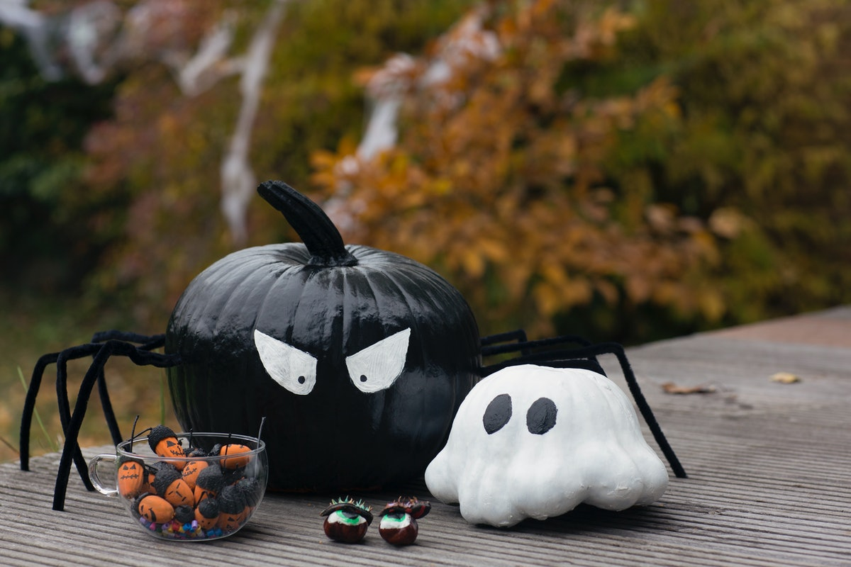Two painted pumpkins, that have been crafted to look like a spider and ghost, sit on a wooden table ...